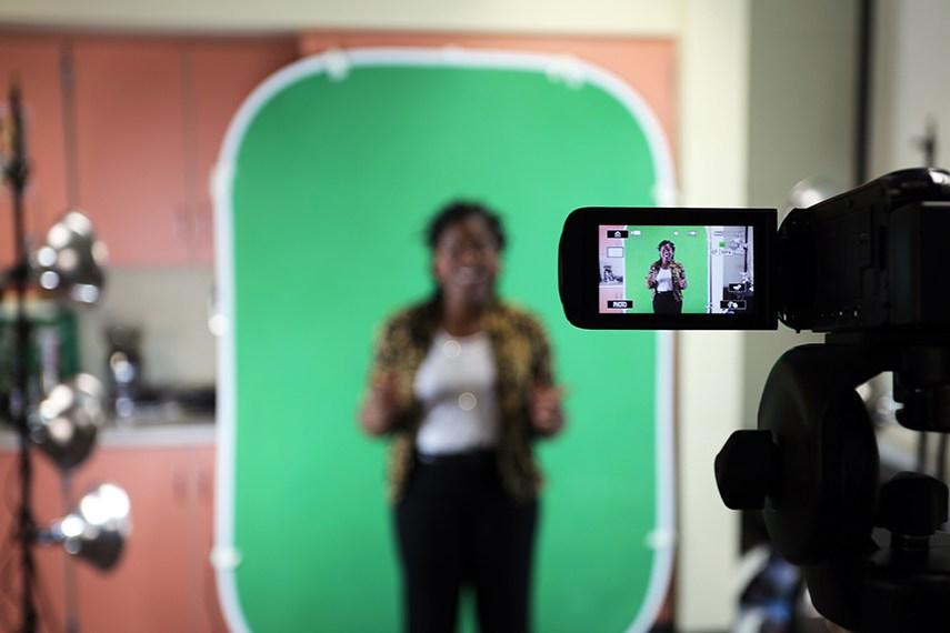 mujer de pie delante de la pantalla verde