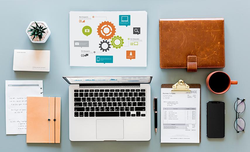 Escritorio con computadora y herramientas y papel con infografía.