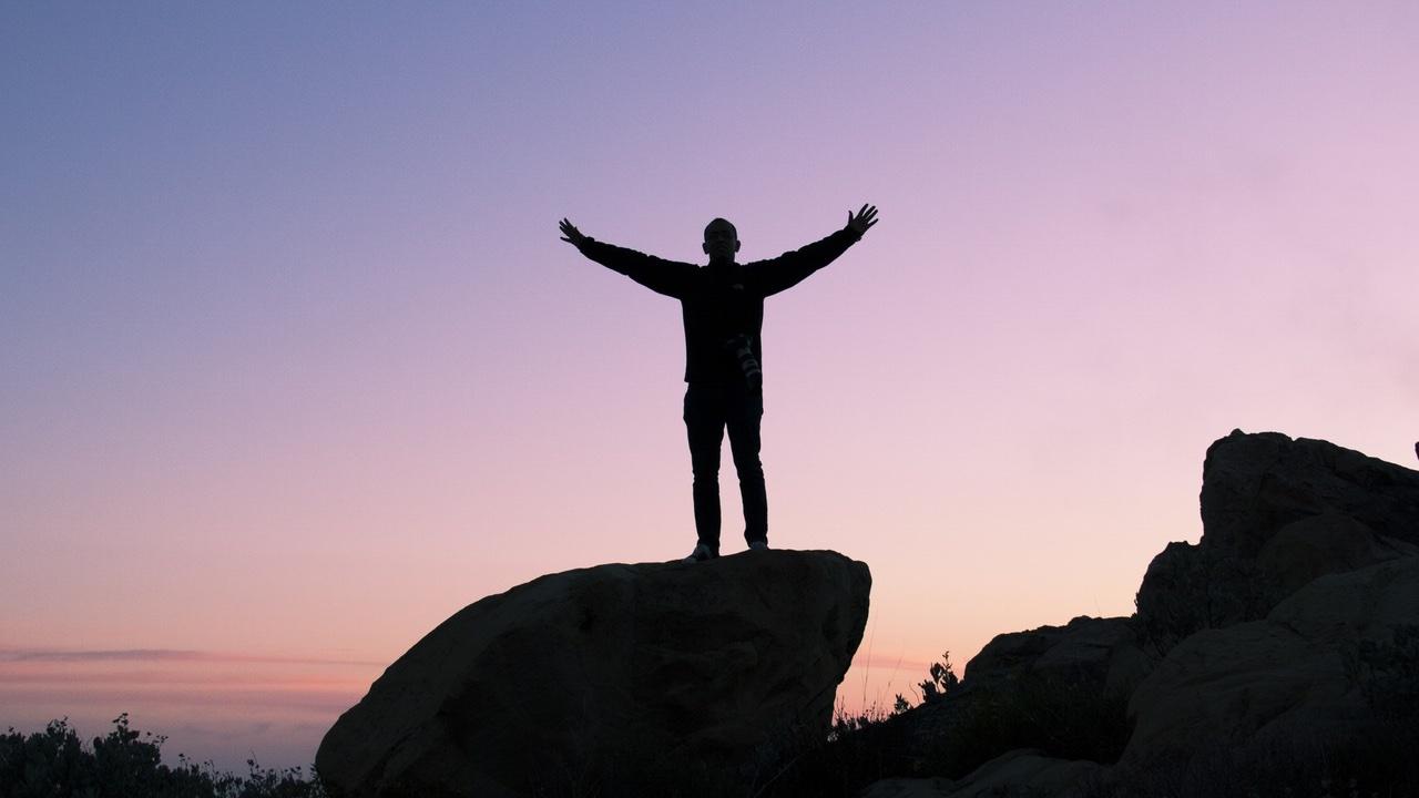 Hombre estar de pie, en, roca, amanecer